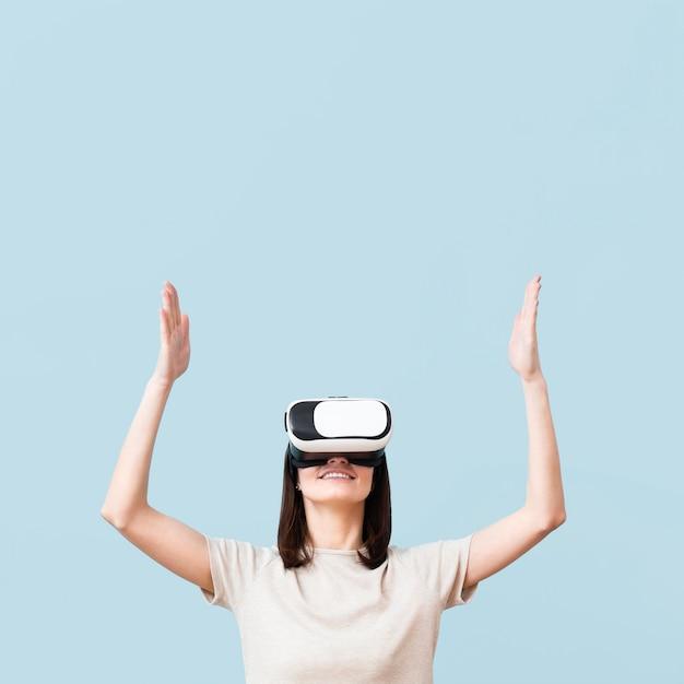 Smiley-frau, die virtual-reality-headset mit kopienraum trägt Kostenlose Fotos