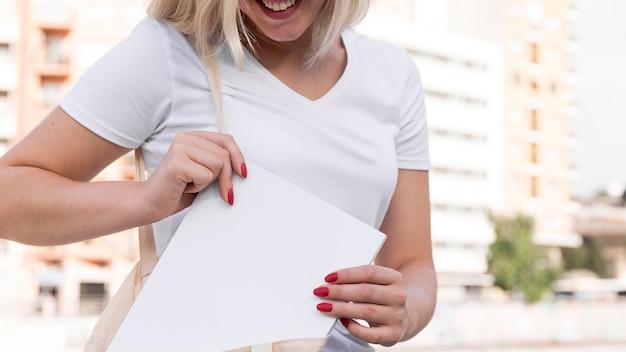 Smiley frau im freien buch in ihre tasche setzen Kostenlose Fotos