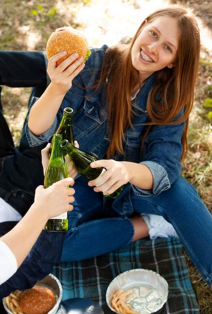 Smiley-frau im park mit burger und bier Kostenlose Fotos