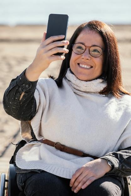 Smiley-frau in einem rollstuhl, der selfie am strand nimmt Kostenlose Fotos