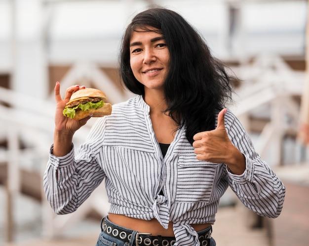 Smiley-frau mit burger, der zustimmung zeigt Kostenlose Fotos