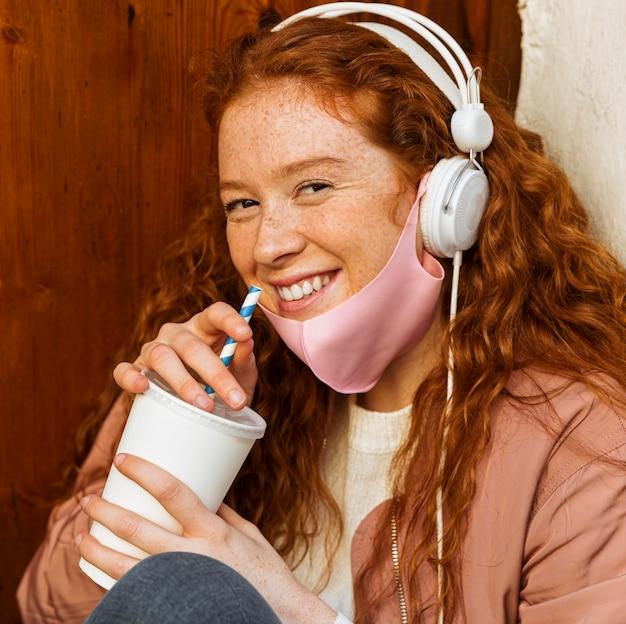 Smiley-frau mit gesichtsmaske im freien und kopfhörern Kostenlose Fotos