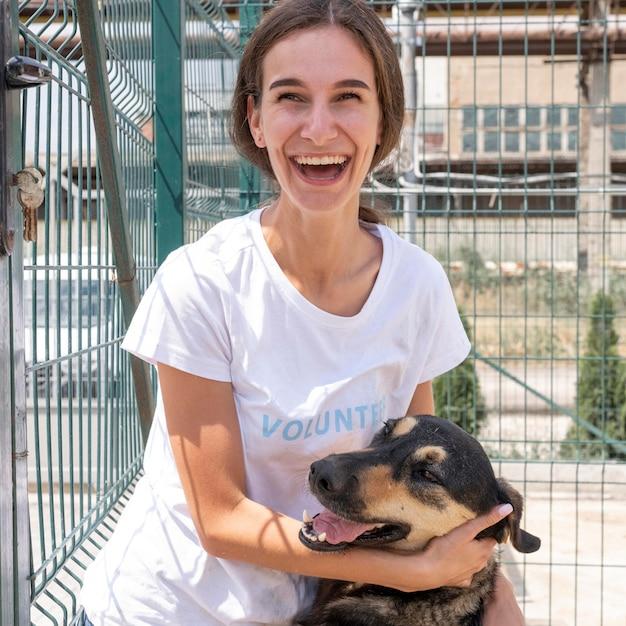 Smiley-frau mit niedlichem hund, der darauf wartet, von jemandem adoptiert zu werden Kostenlose Fotos