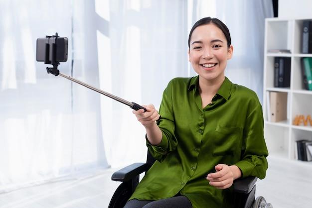 Smiley-frau mit selfie-stick Kostenlose Fotos