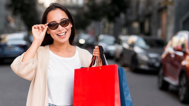 Smiley-frau mit sonnenbrille, die draußen mit einkaufstaschen aufwirft Kostenlose Fotos
