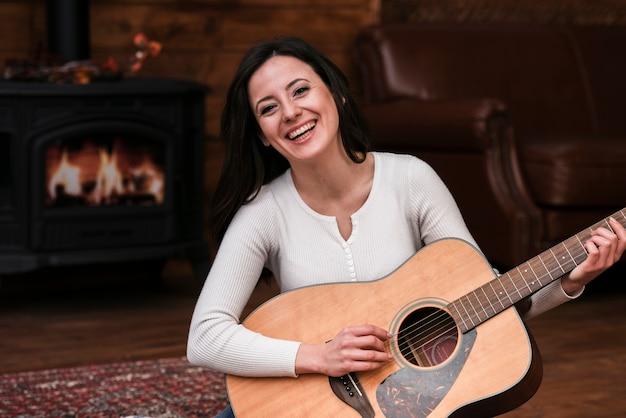Smiley frau spielt gitarre Kostenlose Fotos