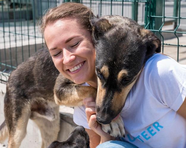 Smiley frau spielt mit niedlichen hund bis zur adoption Kostenlose Fotos