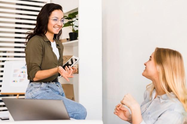 Smiley-frauen im büro sprechen Kostenlose Fotos