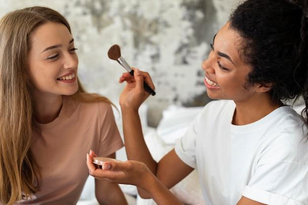 Smiley-freunde helfen sich gegenseitig beim schminken Kostenlose Fotos