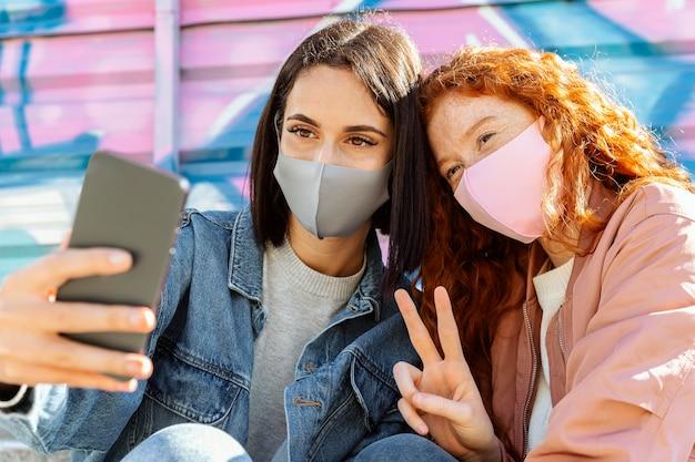 Smiley-freundinnen mit gesichtsmasken im freien machen ein selfie Kostenlose Fotos