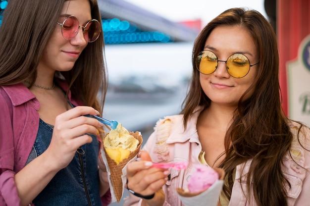 Smiley-freundinnen mit sonnenbrille essen süßigkeiten Kostenlose Fotos