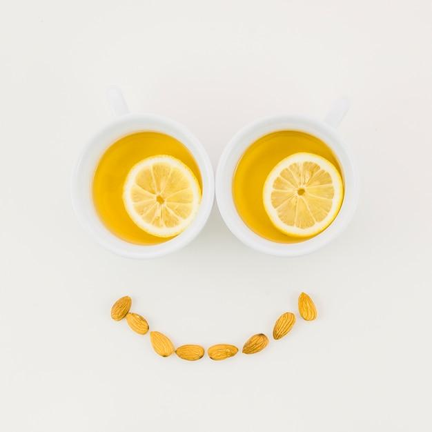 Smiley gemacht mit der zitronenteeschale und -mandeln lokalisiert auf weißem hintergrund Kostenlose Fotos