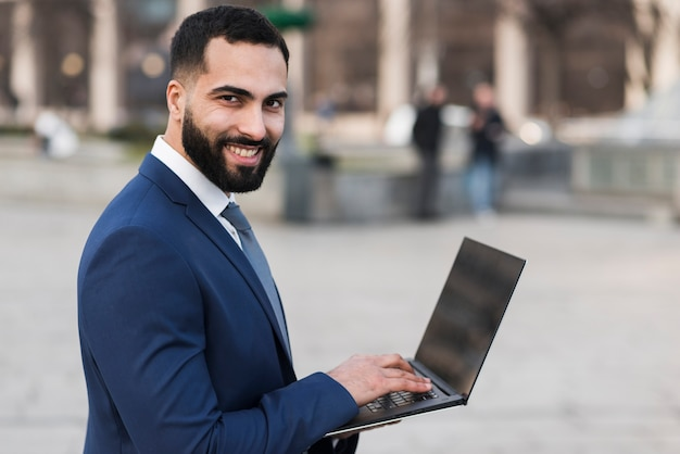 Smiley-geschäftsmann mit laptop Kostenlose Fotos