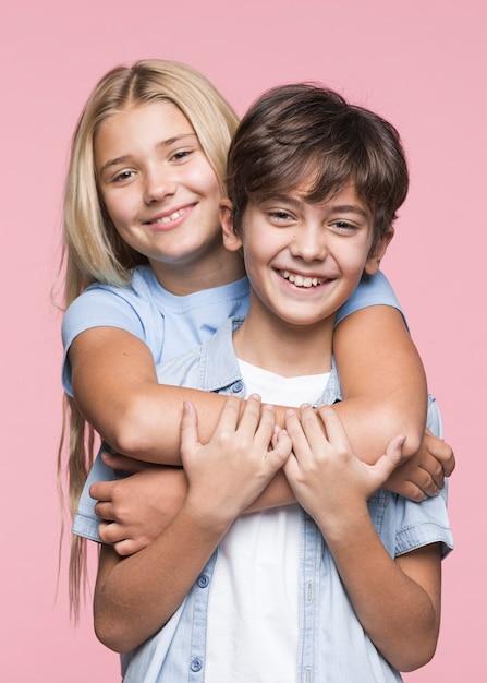 Smiley junge geschwister umarmen Kostenlose Fotos