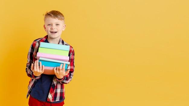 Smiley kleiner junge mit stapel bücher Kostenlose Fotos