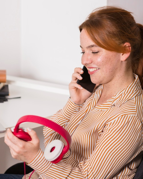 Smiley-lehrer, der auf smartphone spricht und kopfhörer während des online-unterrichts hält Kostenlose Fotos