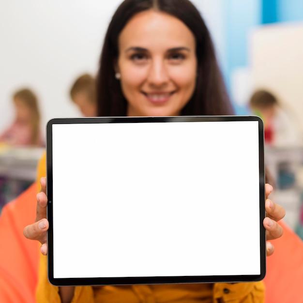 Smiley-lehrer, der eine leere bildschirmtafel hält Kostenlose Fotos
