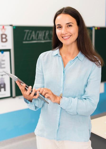 Smiley-lehrer hält eine tablette Kostenlose Fotos