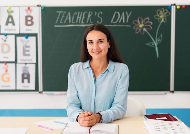 Smiley-lehrerin an ihrem schreibtisch im klassenzimmer Kostenlose Fotos