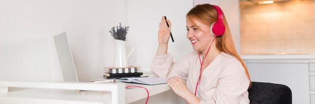 Smiley-lehrerin mit kopfhörern, die eine online-klasse halten Kostenlose Fotos
