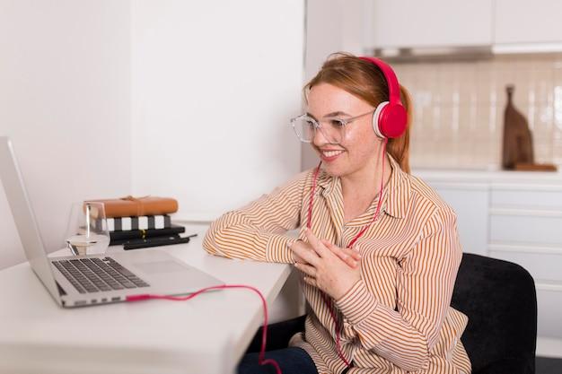 Smiley-lehrerin mit kopfhörern, die online-klasse von zu hause aus halten Premium Fotos