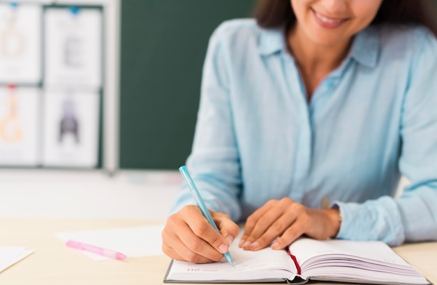 Smiley-lehrerin schreibt in ihr notizbuch Kostenlose Fotos