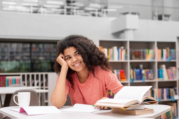 Smiley-mädchen beim bibliotheksstudium Kostenlose Fotos