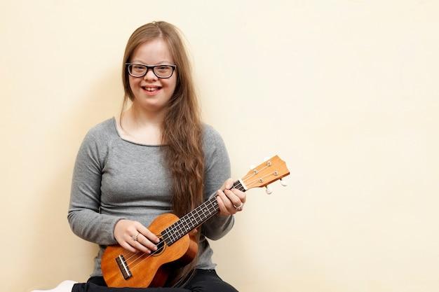 Smiley-mädchen mit down-syndrom hält gitarre Kostenlose Fotos