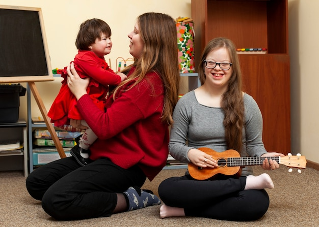 Smiley-mädchen mit down-syndrom und frau, die kind hält Premium Fotos