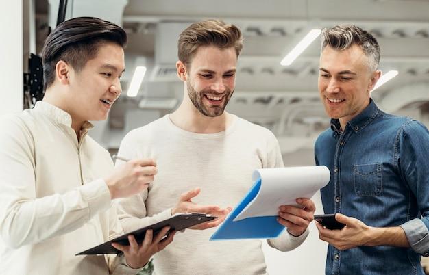 Smiley-männer diskutieren über ein projekt bei der arbeit Kostenlose Fotos