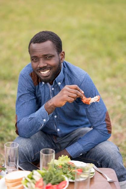 Smiley-mann, der grill draußen isst Kostenlose Fotos