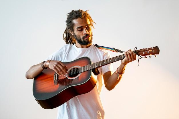 Smiley-mann der vorderansicht, der die gitarre spielt Kostenlose Fotos