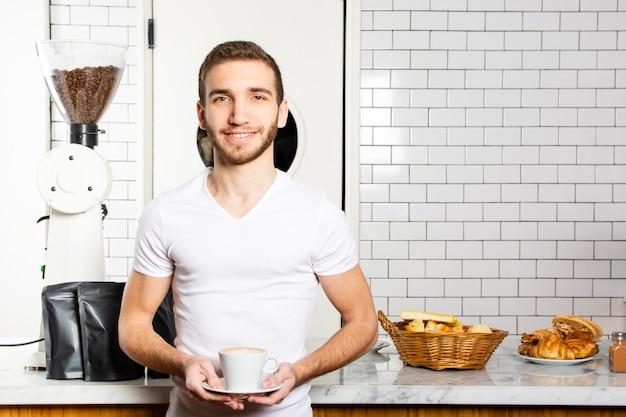 Smiley mann mit einer tasse cappuccino in seinen händen Kostenlose Fotos