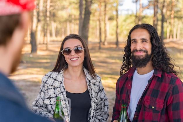 Smiley mann und frau unterhalten sich mit freund im freien Kostenlose Fotos