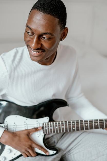 Smiley-musiker mit e-gitarre Kostenlose Fotos
