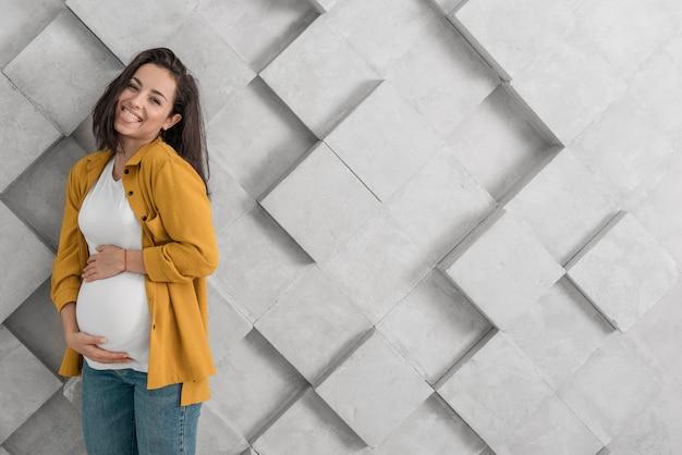 Smiley schwangere frau, die ihren bauch mit kopienraum hält Kostenlose Fotos