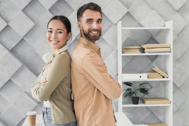 Smiley-team steht im büro Kostenlose Fotos