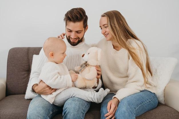 Smiley vater und mutter mit baby zu hause Premium Fotos
