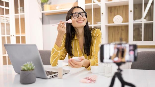Smiley-vloggerin zu hause mit smartphone und pinsel Kostenlose Fotos