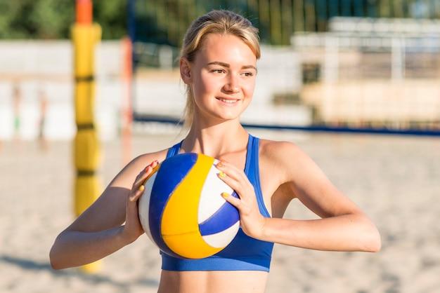 Smiley-volleyballspielerin am strand, die ball hält Kostenlose Fotos