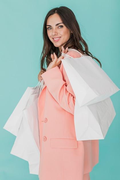 Smileydame in der rosa jacke, die kamera betrachtet Kostenlose Fotos