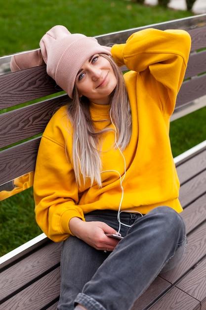 Smileyfrau, die auf bank beim tragen der mütze aufwirft Kostenlose Fotos