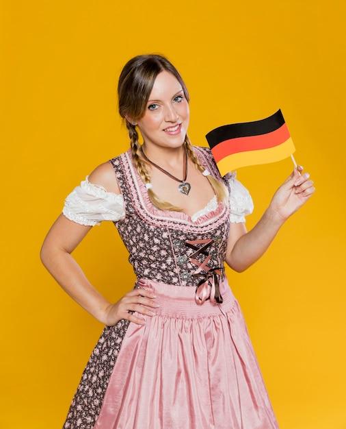 Smileyfrau, die deutsche flagge hält Kostenlose Fotos