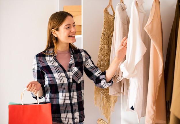 Smileyfrau, die in der garderobe schaut Kostenlose Fotos