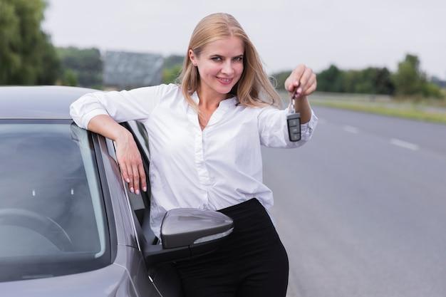 Smileyfrau, die mit autoschlüsseln aufwirft Kostenlose Fotos