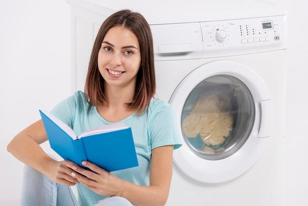 Smileyfrau, die nahe waschmaschine liest Kostenlose Fotos