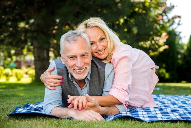Smileyfrau, die seinen mann am picknick umarmt Kostenlose Fotos
