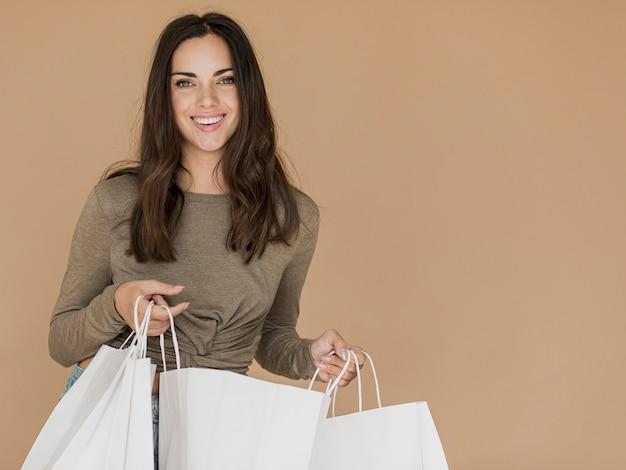 Smileyfrau mit den einkaufstaschen, die zur kamera schauen Kostenlose Fotos