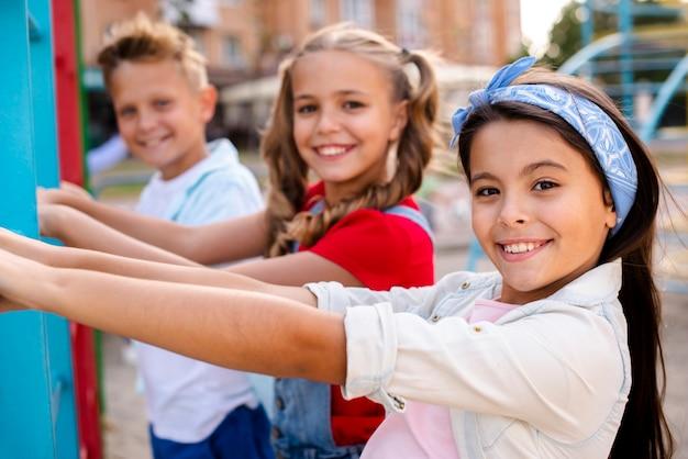 Smileykinder, die auf einem spielplatz spielen Kostenlose Fotos