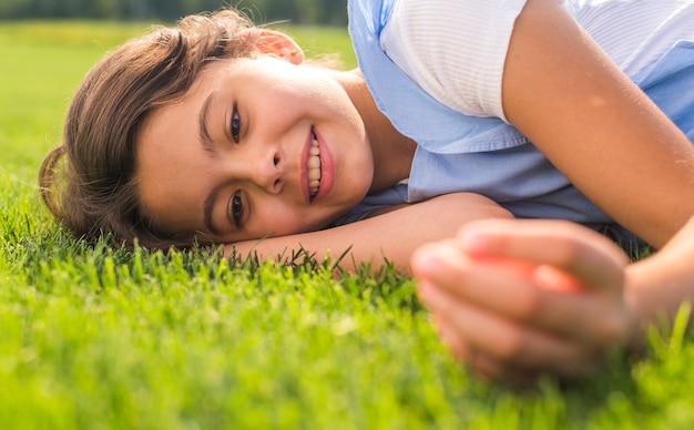 Smileymädchen, das auf gras bleibt Kostenlose Fotos
